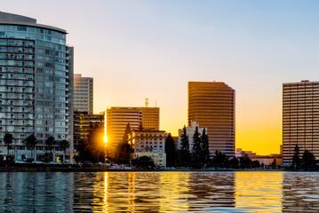 Oakland Lake Merritt skyline backlit at sunset with sun flare be