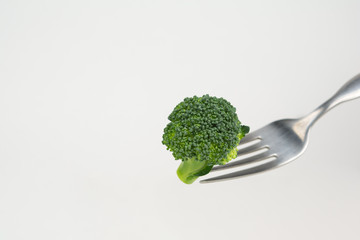 Broccoli on a fork isolated on white background