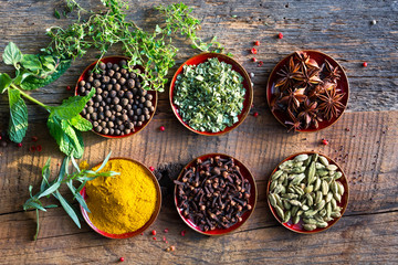 Fresh herbs and spices against rustic boards. Close up with text