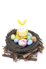 nest with colored Easter eggs and rabbit, isolated