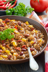 spicy Mexican dish chili con carne in a brown pottery plate