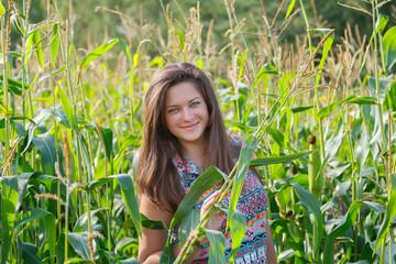 Portrait of young woman at corn field background