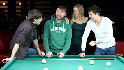 Group of happy friends playing in billiard