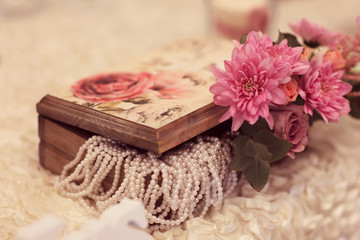 Wooden box with pearls and flower on a wedding table