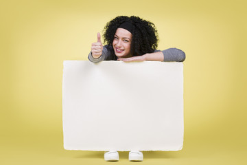 Smiling woman holding a white sign board showing thumbs up