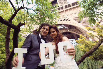 Bride and groom holding I DO letters near Eiffel tower
