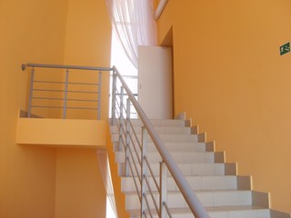 flight of stairs with railings and yellow walls
