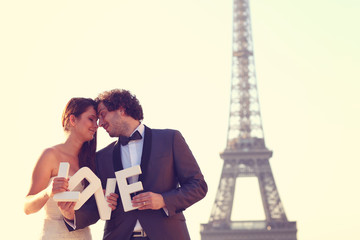 bride and groom holding LOVE letters near Eiffel Tower