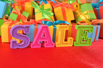 Sale written by colorful letters on the background of gifts