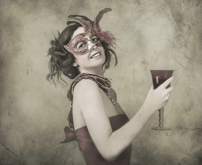 Woman in mysterious venetian mask with glass of wine