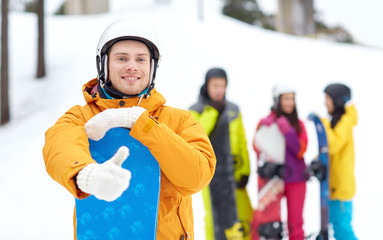 happy young man with snowboard showing thumbs up