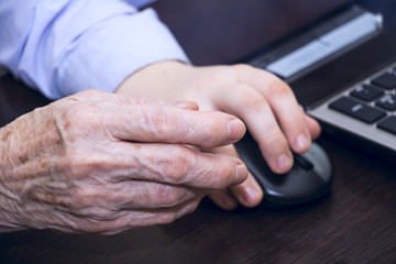 Hand of an elderly woman and a boy's hand holding a computer mou
