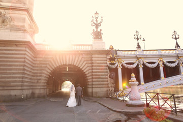 Bride and groom in the sunlight near a bridge