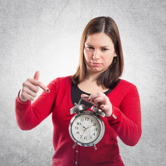 Young girl pointing an antique clock over white background