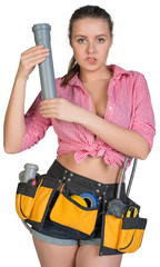 Woman in tool belt holding fitting pipe