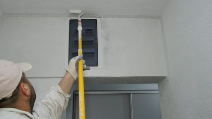 Worker painting wall to white with paint roller