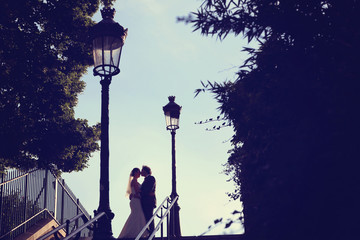 Bride and groom kissing at sunset in Paris, France