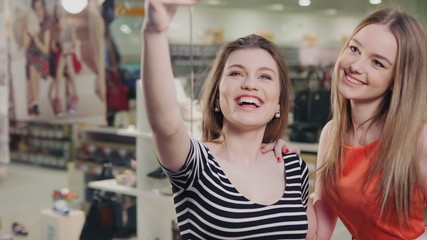 """Beautiful girls with shopping bags taking a """"selfie"""" with their"""