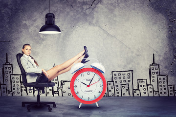 Businesswoman sitting with her feet up on alarm-clock