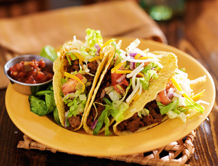 platter of three beef mexican tacos with cheese and lettuce