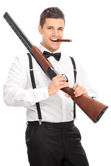 Young man holding a rifle and smoking cigar