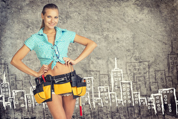 Woman in tool belt standing akimbo against stone wall with