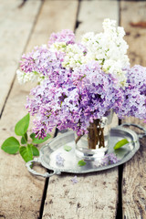 Bouquet of lilac flowers in vase on wooden background, toned