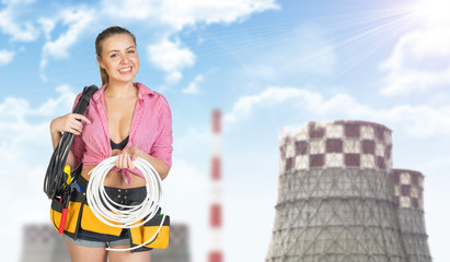 Woman in tool belt holding coils of cable