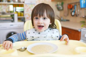 little child age of 2 years eats wheat porridge with pumpkin
