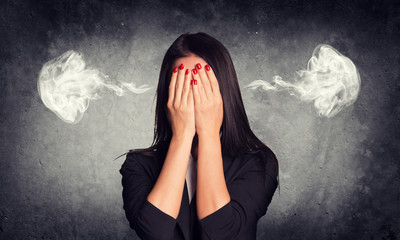 Close-up portrait of businesswoman hiding face in her hands