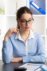 Young female bookkeeper calculating company's profit and loss