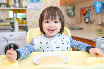 Portrait of happy little child eating wheat porridge