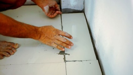 Close up male hands laying ceramic floor tiles. Macro video