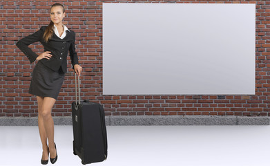 Businesswoman with travel bag against brick wall