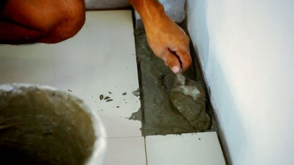 Closeup male hands laying ceramic floor tiles. Macro video time