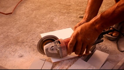 Close up of craftsman is cutting floor tile with portable angle