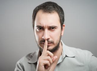 Man gesturing silent. Quiet.