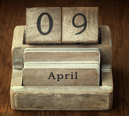 A very old wooden vintage calendar showing the date 9th April on