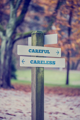Rustic wooden sign in an autumn park with the words Careful - Ca