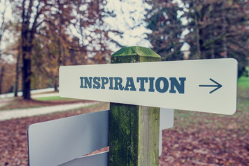 Inspiration signboard on a wooden post with a right pointing arr