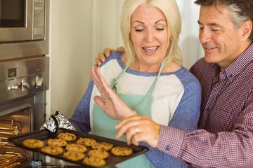 Woman taking tray of fresh cookies out of oven with husband