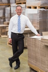 Smiling boss leaning on stack of cartons