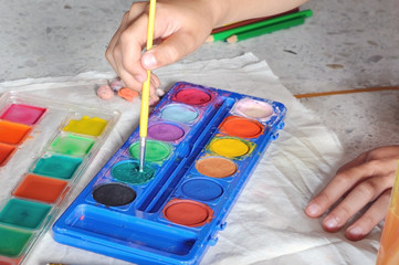 child hand choose color from watercolor paint pallet