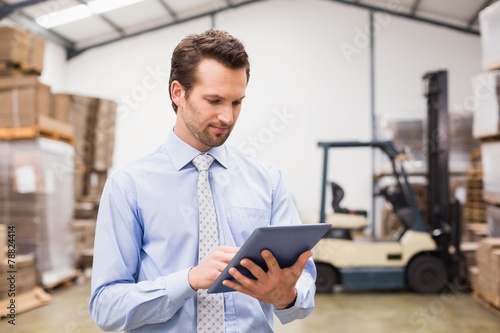 canvas print picture Manager using digital tablet in warehouse