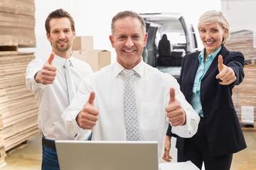 Warehouse team smiling at camera showing thumbs up