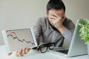Depressed businessman leaning head below bad stock market chart