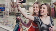 Two happy friends is taking selfie while shopping in mall