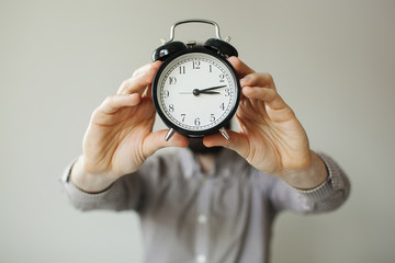Man with alarm clock head in hands