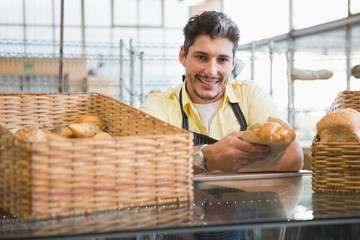 Smiling server in apron holding bread