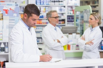 Pharmacist in lab coat writing a prescription
